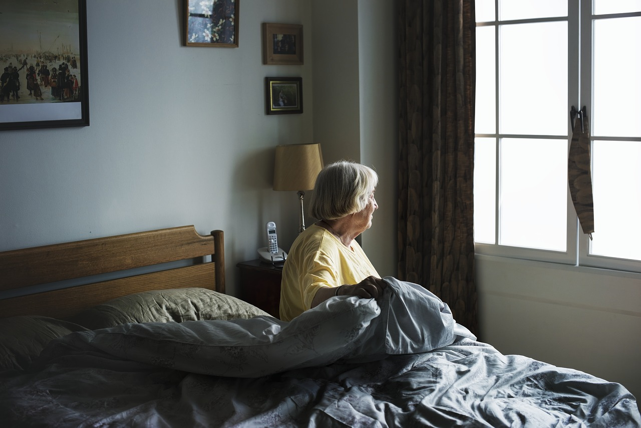 assisted living apartments senior woman in bed looking out window