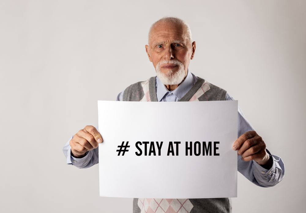 stay at home senior man holding sign that says stay at home