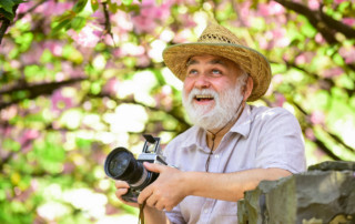 photography benefits for Alzheimer's senior man with camera outside happy