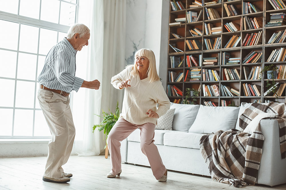Senior man and woman dancing in living room in front of large bookcase and sofa with large window next to them letting in natural light