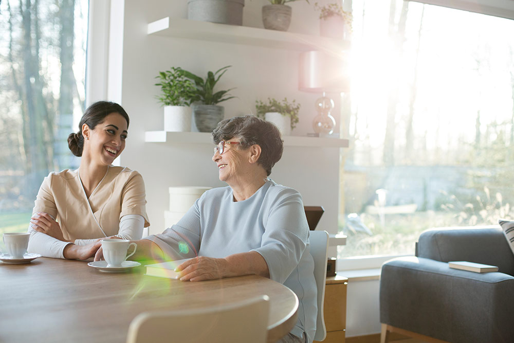 Woman caregiver with senior woman sitting down at a table in a naturally lit room
