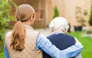 Caregiver walking with arm around senior