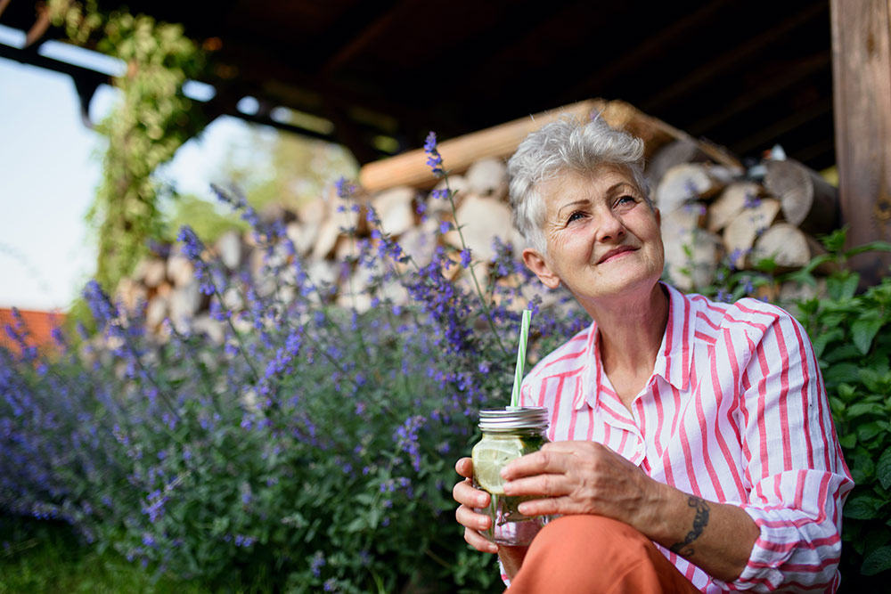 Senior woman sitting on front porch steps with glass of water enjoying the outdoors