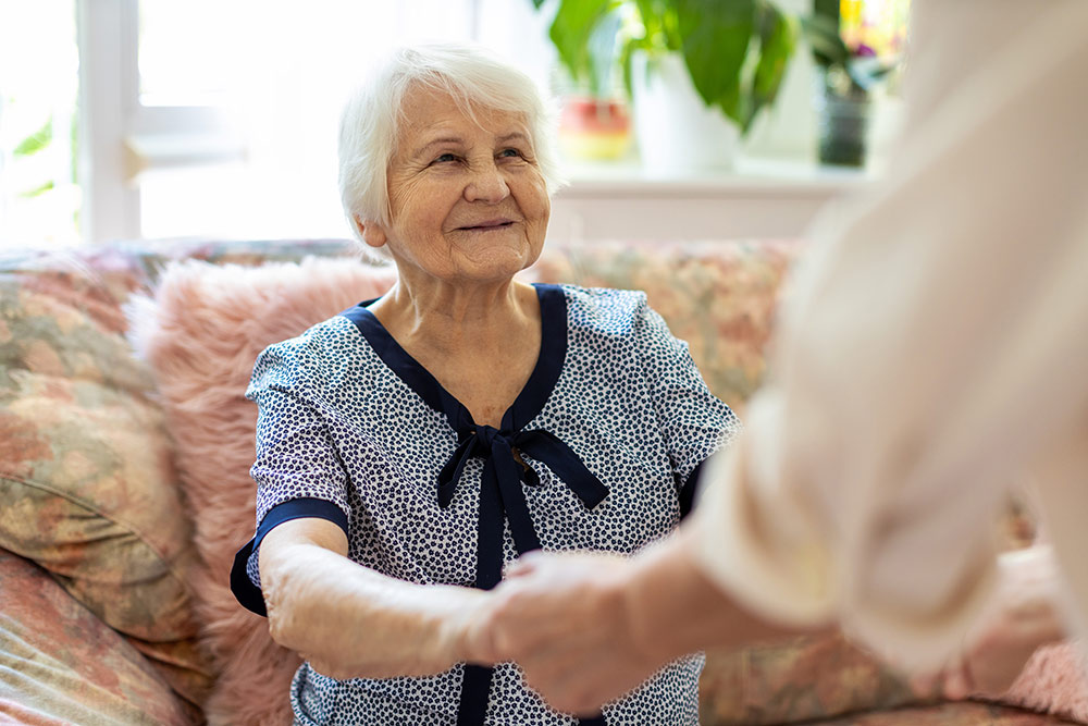 Senior woman smiling and looking up at caregiver