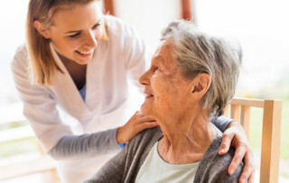 Senior woman in chair looking up and smiling at caregiver in assisted living facility