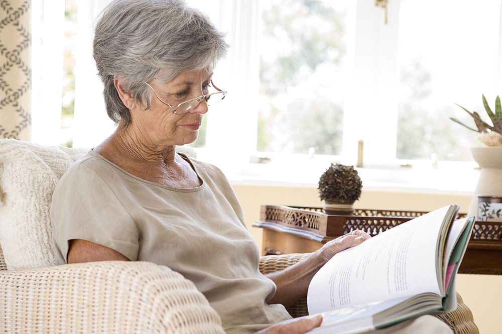 Senior woman reading book on couch at home in living room