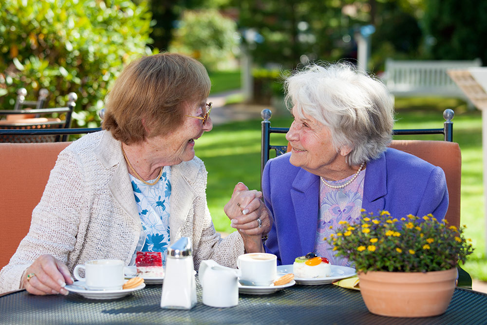 Two senior woman smiling and enjoying lunch on a patio outside in the sun at assisted living facility