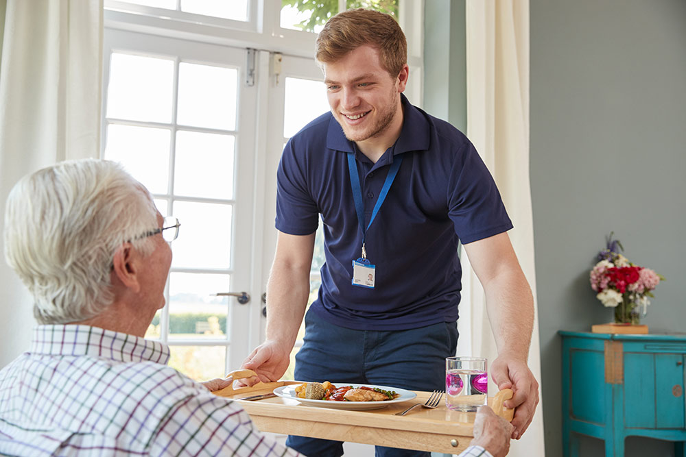 Senior man with Alzheimer's receiving food from caregiver in Alzheimer's assisted living facility