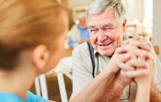 Happy senior man with caregiver at dementia memory care facility