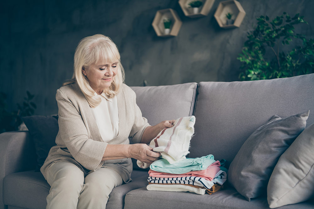 Senior woman with dementia sitting on couch folding laundry
