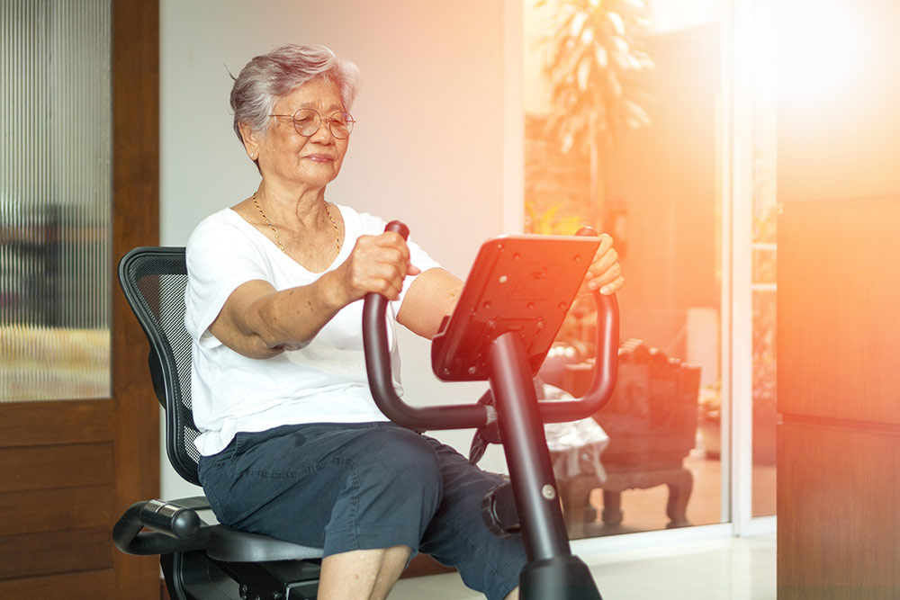Senior woman on stationary bike exercising