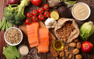 Board with healthy foods spread out on it from salmon to nuts, grains, and vegitables