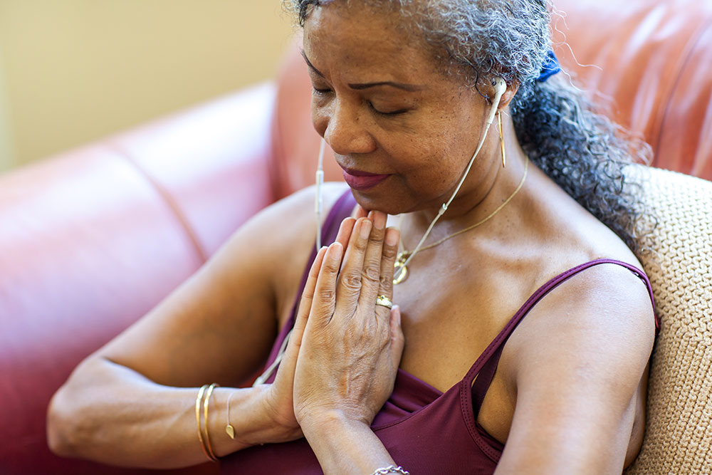 Senior woman meditating with headphones in listening to calming music