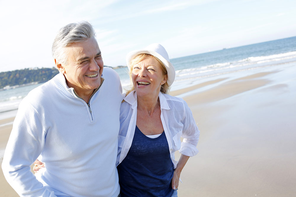 Senior couple walking along beach smiling and happy