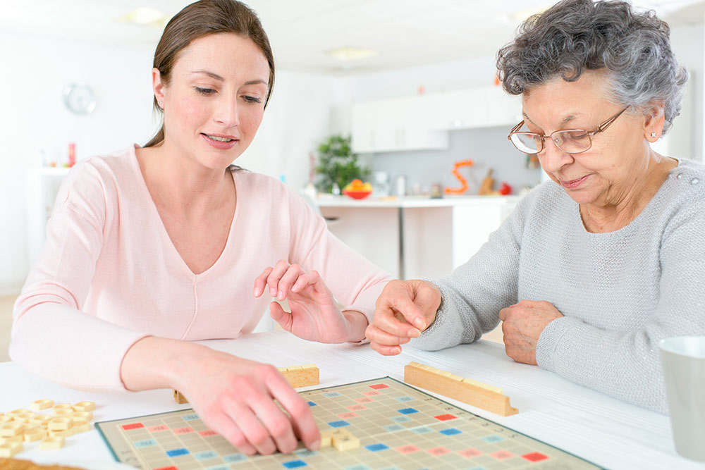 Woman with senior mother playing board game