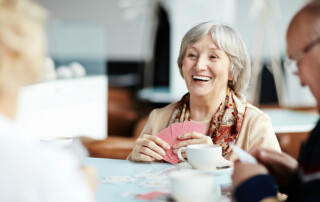Senior woman happy and smiling playing cards in assisted living home