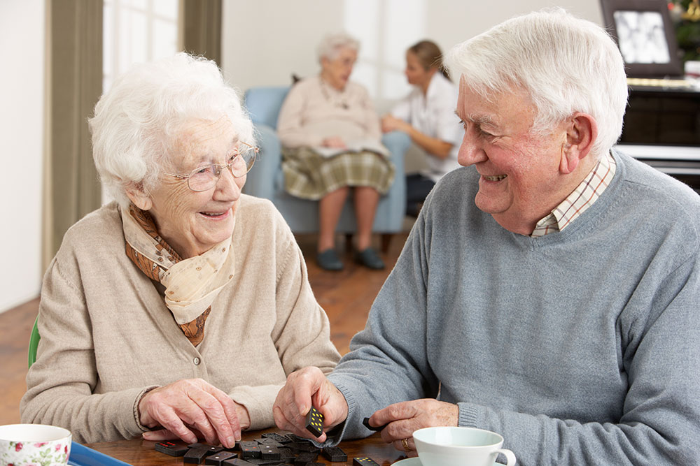 Happy, smiling couple sitting at table playing dominoes in alzheimer's assisted living