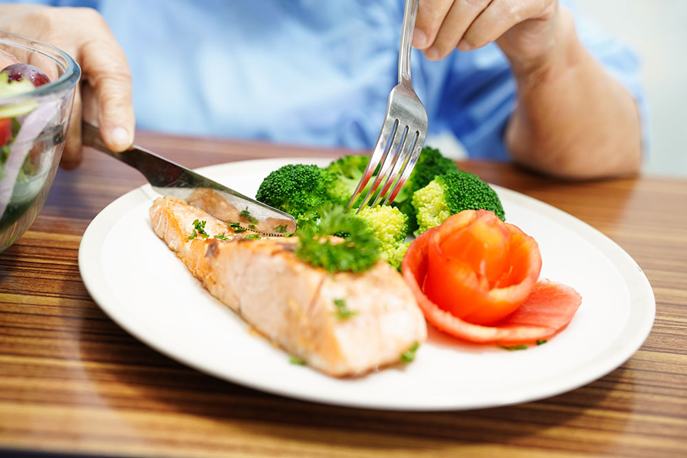 Close up of senior eating healthy plate of food