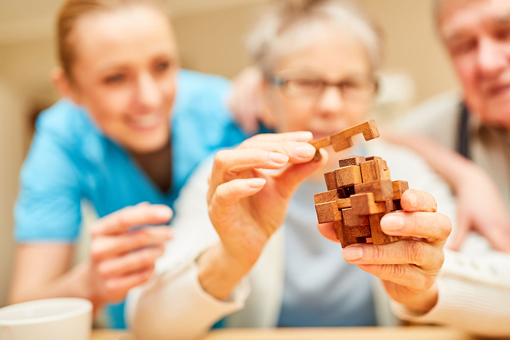 Senior woman with Alzheimer's doing puzzle with caregiver in assisted living