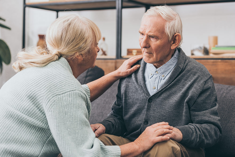 Senior man sitting on couch with worried look, senior woman comforting man
