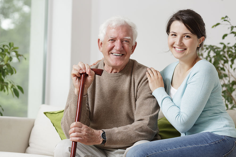 Senior man holding cane sitting on couch next to daughter