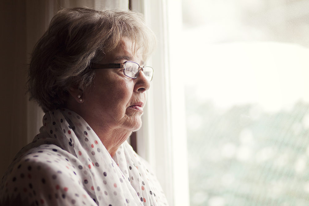 Senior woman with worried look looking out window