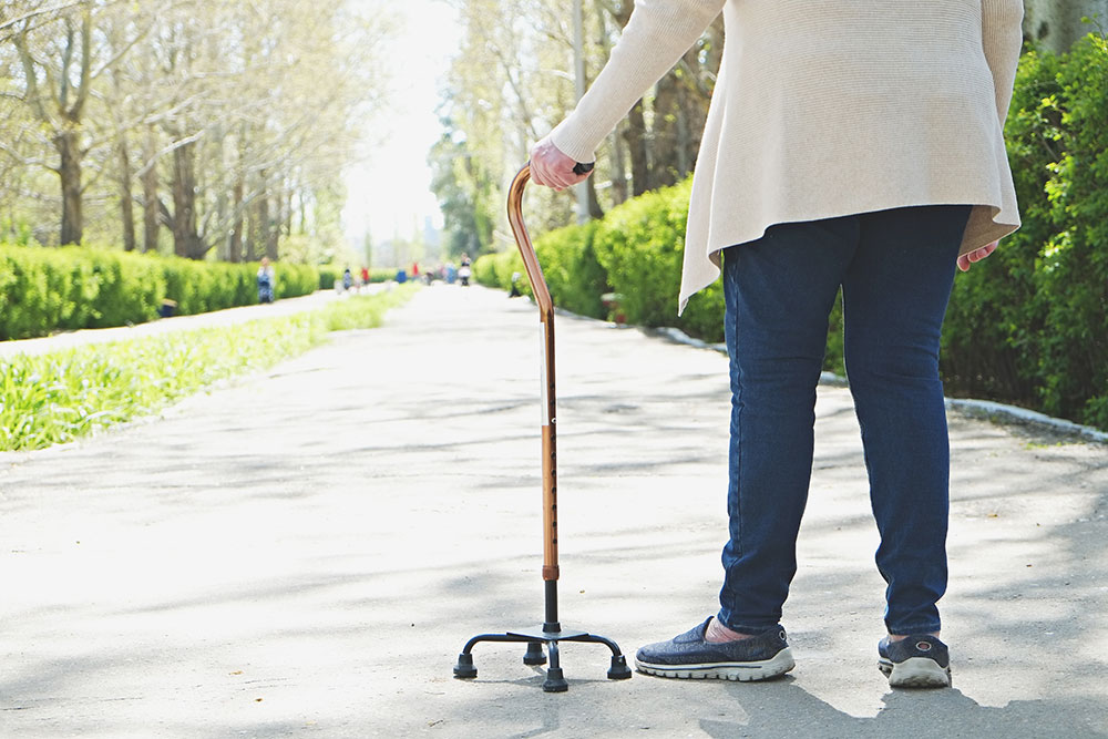 Senior woman walking outside on path with cane walker