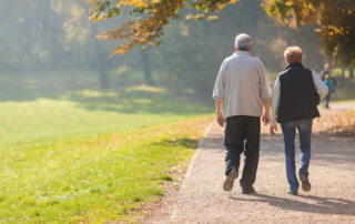 An elderly couple taking a walk on a fall afternoon.